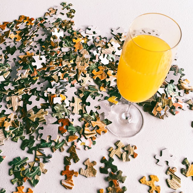 Pile of puzzle pieces and a glass of mimosa