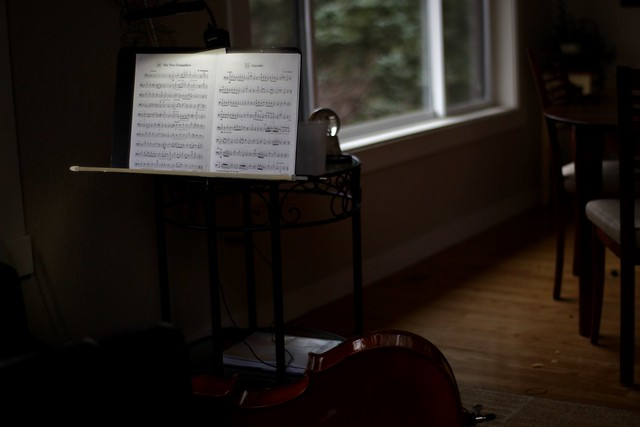 dark room with lit music stand holding sheet music