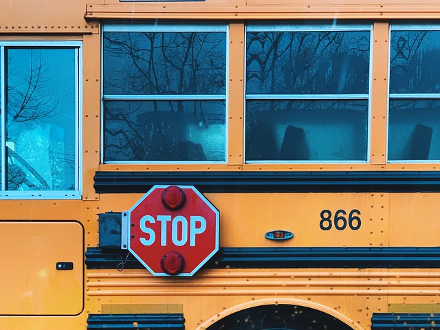closeup of a schoolbus with Stop sign in view