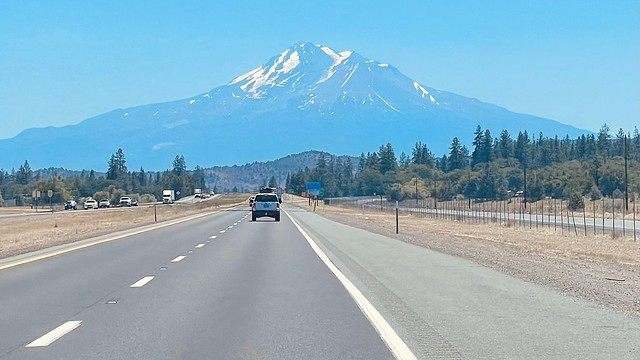 A freeway with a vehicle  driving toward a looming mount shasta