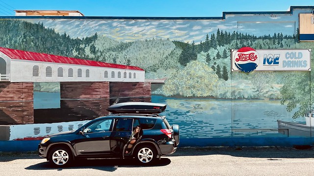 A Toyota RAV4 parked in front of building mural with covered bridge, forest landscape, and Pepsi ad