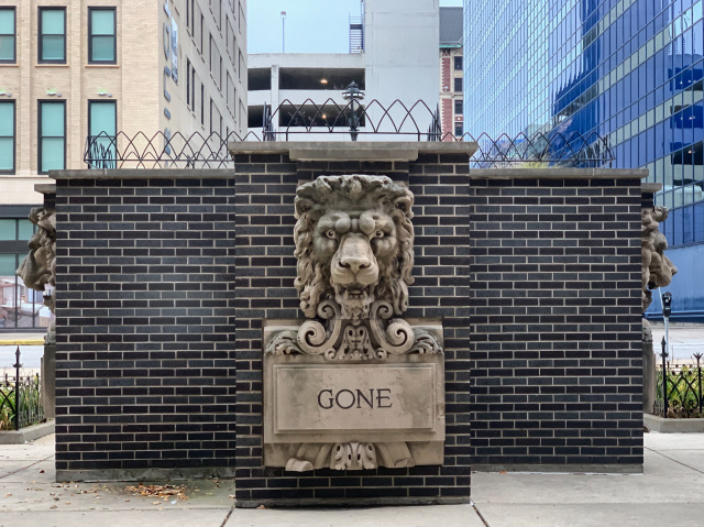 Lion statue on brick memorial with engraved word: gone