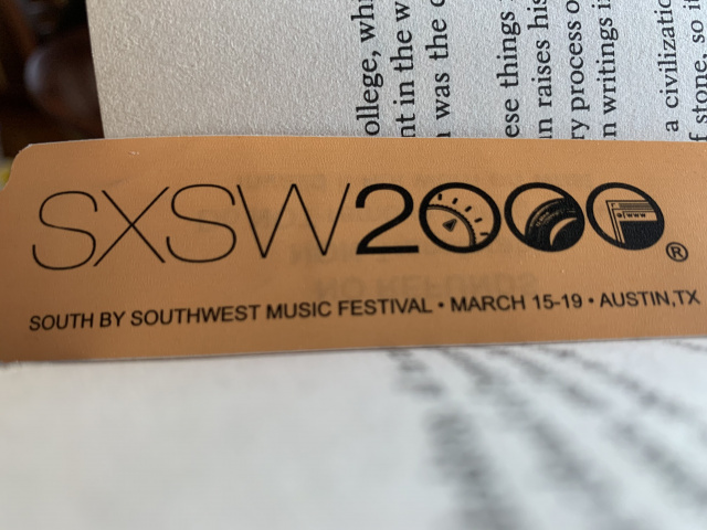 photo of an orange south by southwest music festival wristband in the spine of a book