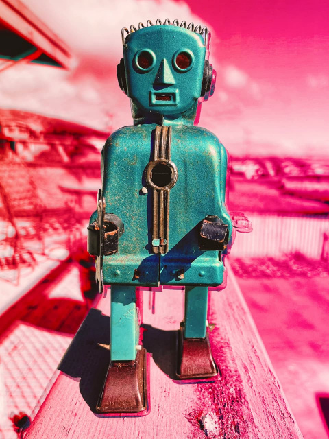 an old wind-up robot toy on a colorful digitally altered background